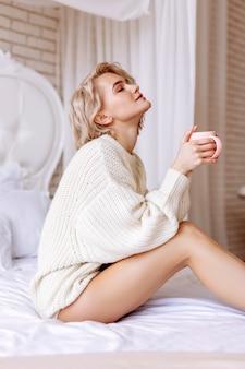 Chillen in bed. slanke vrouw met blond haar die in het weekend in bed ligt te chillen terwijl ze wat koffie drinkt