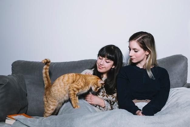 Chillen meisjes met harige speelse kat