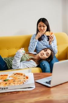 Chillende meisjes kijken naar film en pizza eten