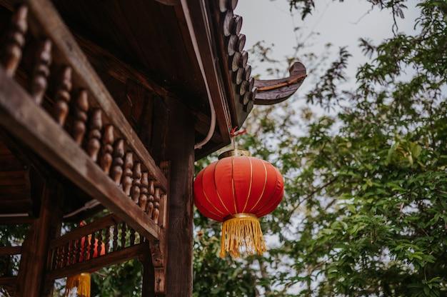China reist chinese rode lantaarns die op een houten pagode of een gazebo in aardpark hangen voor de chinese banner van de nieuwjaar maanviering