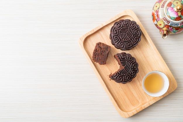 Chinees donkere de chocoladesmaak van de maancake op houten plaat