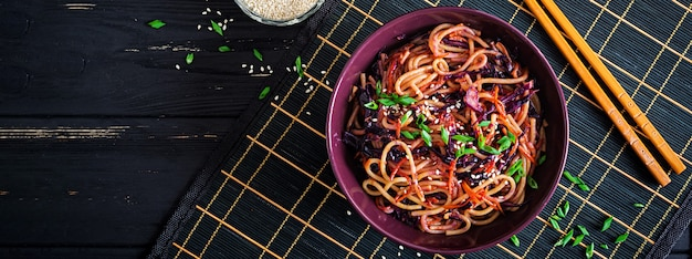 Chinees eten. de veganist beweegt gebraden gerechtnoedels met rode kool en wortel in een kom op een zwarte houten achtergrond. aziatische keukenmaaltijd. banner. bovenaanzicht