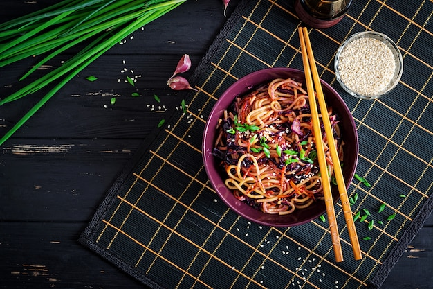 Chinees eten. de veganist beweegt gebraden gerechtnoedels met rode kool en wortel in een kom op een zwarte houten achtergrond. aziatische keukenmaaltijd. bovenaanzicht