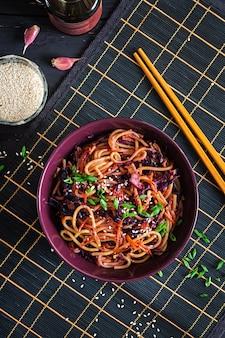Chinees eten. de veganist beweegt gebraden gerechtnoedels met rode kool en wortel in een kom op een zwarte houten achtergrond.