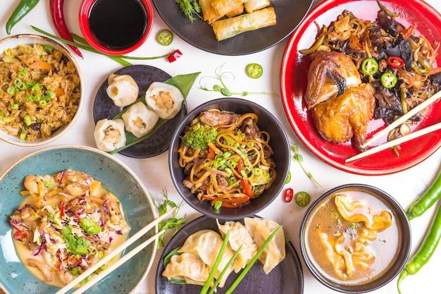 Chinees eten donkere achtergrond. chinese noedels, rijst, dumplings, pekingeend, dim sum, loempia's