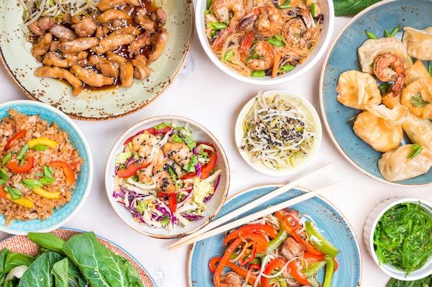 Chinees eten op witte achtergrond. bami, gebakken rijst, dumplings, roerbak kip, dim sum, loempia