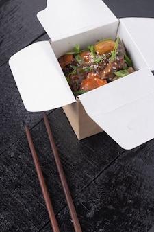 Chinees eten van zoetzure, sinaasappel- of citroenkip - in een afhaalcontainer met chopsticsk