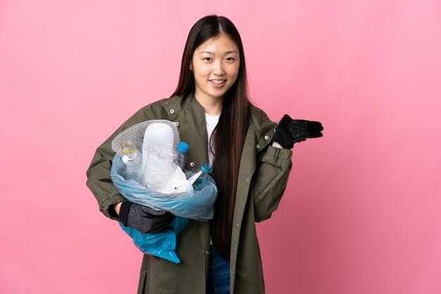 Chinees meisje die een zakhoogtepunt van plastic flessen houden om op geïsoleerde roze holding copyspace denkbeeldig op de palm te recycleren om een advertentie op te nemen