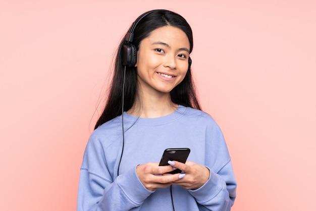 Chinees meisje geïsoleerd op roze muur luisteren muziek met een mobiele telefoon en op zoek voorzijde