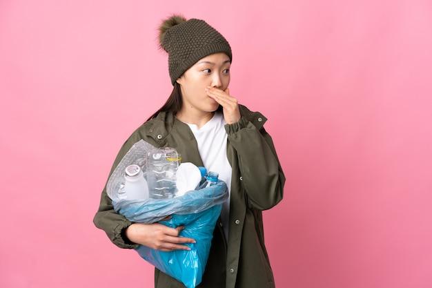 Chinees meisje met een zak vol plastic flessen om te recyclen over geïsoleerde roze muur doet verrassingsgebaar terwijl ze naar de zijkant kijkt