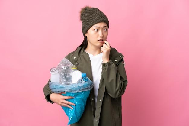 Chinees meisje met een zak vol plastic flessen om te recyclen over geïsoleerde roze muur nerveus en bang