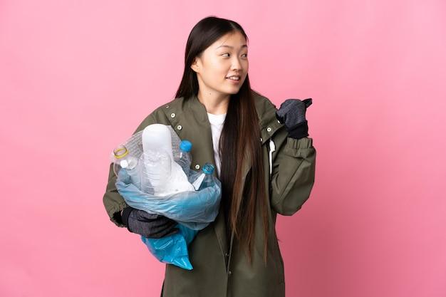 Chinees meisje met een zak vol plastic flessen om te recyclen over geïsoleerde roze muur wijzend naar de zijkant om een product te presenteren
