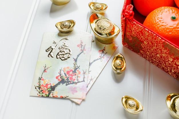 Chinees nieuw jaar, rood enveloppakket (ang pow) met gouden blokken en sinaasappelen en bloem