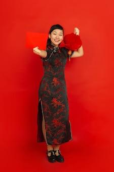 Chinees nieuwjaar 2020. het portret van het aziatische jonge meisje dat op rode achtergrond wordt geïsoleerd. vrouwelijk model in traditionele kleding ziet er blij uit met decoratie en rode envelop. viering, vakantie, emoties.