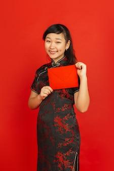 Chinees nieuwjaar 2020. het portret van het aziatische jonge meisje dat op rode achtergrond wordt geïsoleerd. vrouwelijk model in traditionele kleding ziet er gelukkig uit, glimlachend en houdt rode envelop vast. viering, vakantie, emoties.