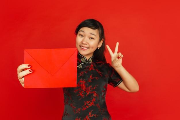 Chinees nieuwjaar 2020. het portret van het aziatische jonge meisje dat op rode achtergrond wordt geïsoleerd. vrouwelijk model in traditionele kleding ziet er gelukkig uit, lacht en toont rode envelop. viering, vakantie, emoties.