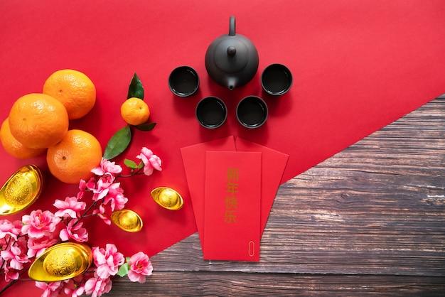 Chinees nieuwjaar dat de rode pot en de sinaasappelen van de envelop chinese thee aanbiedt