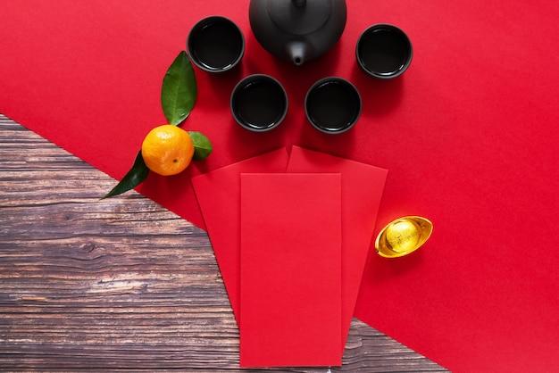 Chinees nieuwjaar dat rode envelop en chinese theepot aanbiedt