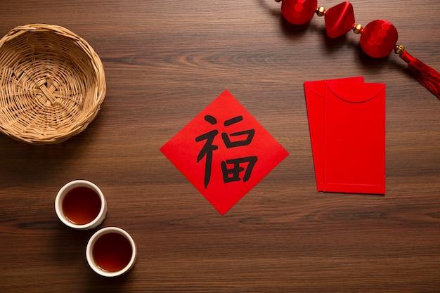 Chinees nieuwjaar en lunar new year-vieringen met goudstaaf die rode envelop en hete thee geeft. het chinese woord betekent: zegen, geluk en geluk