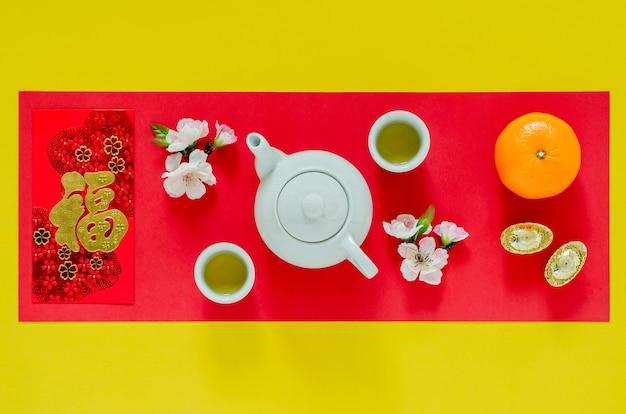 Chinees nieuwjaar geel en rood oppervlak met theeservies, chinese bloesembloemen, goudstaven, sinaasappels en rood enveloppakket of ang bao (woord betekent rijkdom).
