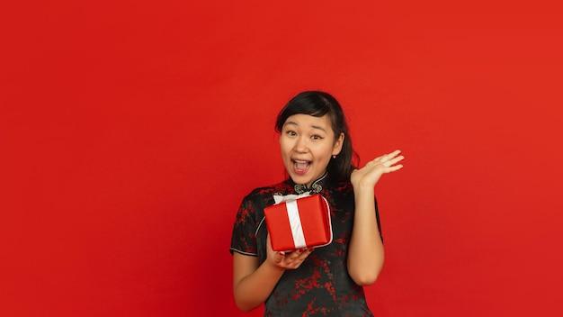 Chinees nieuwjaar. het portret van het aziatische jonge meisje dat op rode achtergrond wordt geïsoleerd. vrouwelijk model in traditionele kleding ziet er blij, glimlachend en verrast uit door een geschenkdoos. viering, vakantie, emoties.
