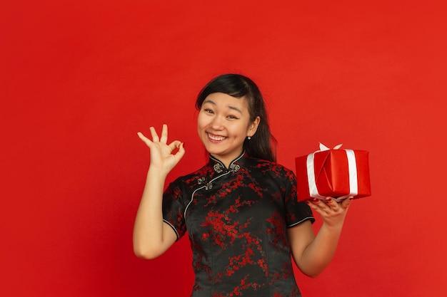 Chinees nieuwjaar. het portret van het aziatische jonge meisje dat op rode achtergrond wordt geïsoleerd. vrouwelijk model in traditionele kleding ziet er blij uit met geschenkdoos. viering, vakantie, emoties. mooi laten zien, glimlachend.