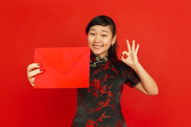 Chinees nieuwjaar. het portret van het aziatische jonge meisje dat op rode achtergrond wordt geïsoleerd. vrouwelijk model in traditionele kleding ziet er gelukkig uit, lacht en toont rode envelop. viering, vakantie, emoties.