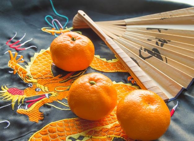Chinees nieuwjaar, mandarijnen en een fan liggend op de zijden stof met een geborduurde draak