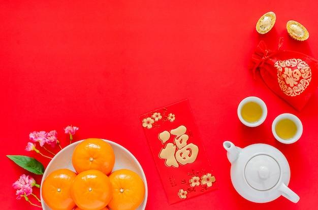 Chinees nieuwjaar rode achtergrond met goudstaven, rode zak (woord betekent rijkdom), theeservies, rood enveloppakket of ang bao (woord betekent rijkdom), sinaasappels en chinese bloesembloemen.