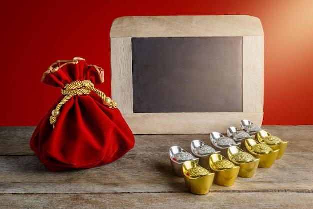 Chinees nieuwjaar rode stoffen tas, ang pow en schoolbord met chinees geluk en schoenvormige goudstaaf