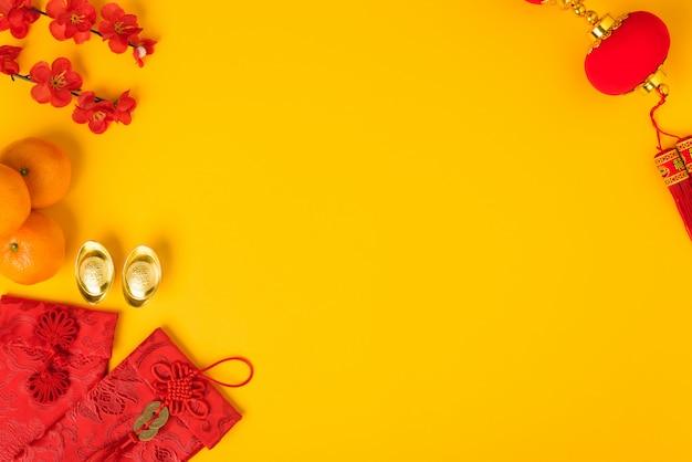 Chinees nieuwjaarfestival, plat lag bovenaanzicht, gelukkig chinees nieuwjaar met rode envelop en goudstaaf op geel en copyspace