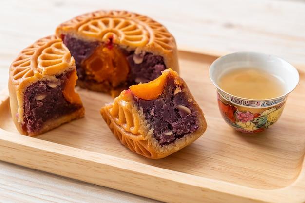 Chinees paars de zoete aardappelsmaak van de maancake met thee op houten plaat