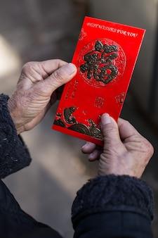 Chinees wijfje dat een traditionele rode envelop met chinese nieuwjaarswensen houdt