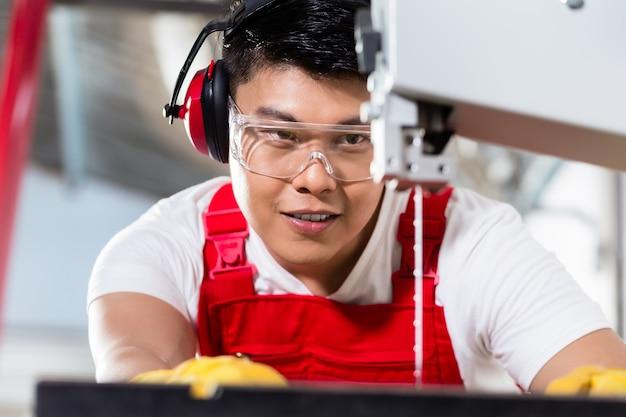 Chinese arbeider op zaag in industriële fabriek die een werkstuk snijdt