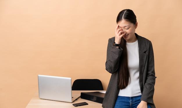 Chinese bedrijfsvrouw in haar werkplaats lachen