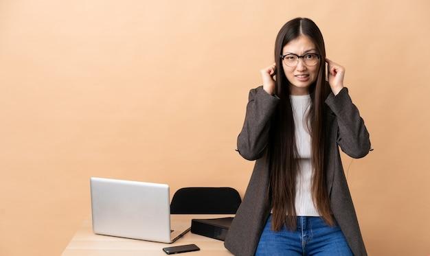 Chinese bedrijfsvrouw op haar gefrustreerde en behandelende werkplaats oren