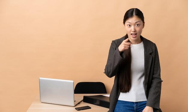 Chinese bedrijfsvrouw op haar werkplaats verrast en wijst naar voren