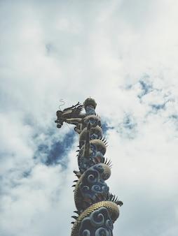 Chinese draak grijpt de post op de hemel backgronds