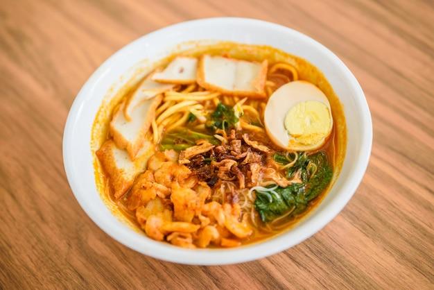 Chinese eetstokjes die noedel, een beroemde soep van de garnalennoedel van maleisië eten.