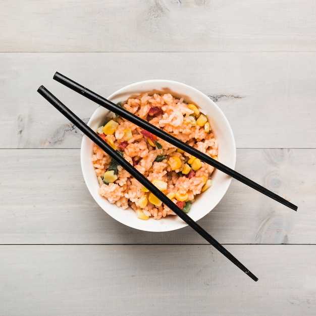 Chinese gebraden rijstkom met zwarte eetstokjes op houten lijst