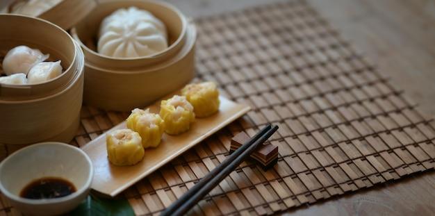 Chinese gestoomde bol en gestoomd varkensvleesbroodje in een bamboestoomboot met eetstokje