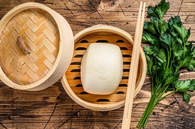 Chinese gestoomde broodjes in traditionele bamboestoomboot. houten achtergrond. bovenaanzicht.