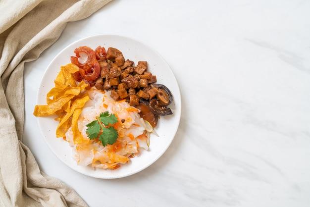 Chinese gestoomde rijstnoedel met varkensvlees en tofu in ketjap