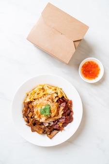 Chinese gestoomde rijstnoedels met pikante saus en bezorgdoos - aziatische voedselstijl