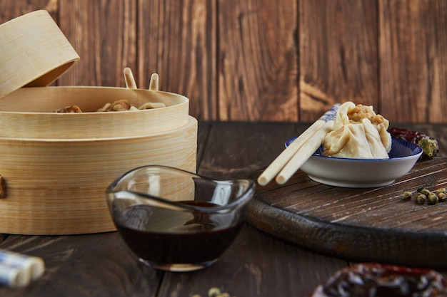 Chinese gestoomde schotel met vleesbol in bamboestoomdoos met eetstokjes en dimsum.