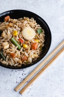 Chinese groente gebakken rijst en eieren geserveerd in een kom met stokjes. chinese keuken