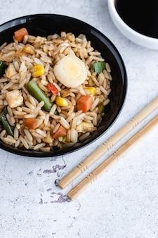Chinese groente gebakken rijst en eieren geserveerd in een kom met stokjes en saus soja. chinese keuken