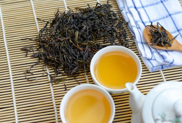 Chinese hete thee in witte kop met theeblad en houten lepel op lijst
