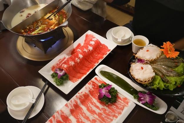 Chinese hotpot-shabu kruidige en zure soep met vlees en zeevruchten, suki chinese-stijl - selectieve nadruk