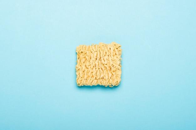 Chinese instant noedels op een blauwe ondergrond. het concept gemaksvoedsel, fast food, junk food. plat lag, bovenaanzicht.
